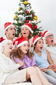 Extended family singing christmas carols together on couch poster