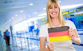 woman holding a german flag in the airport poster