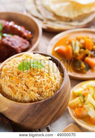 Indian meal biryani rice, chicken curry, acar vegetable, roti chapatti and papadom.