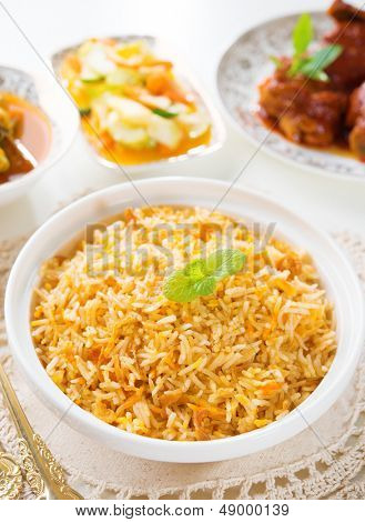 Biryani rice or briyani rice, curry chicken and salad, traditional indian food on dining table. poster