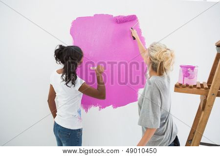 Happy young housemates painting wall pink in their new home