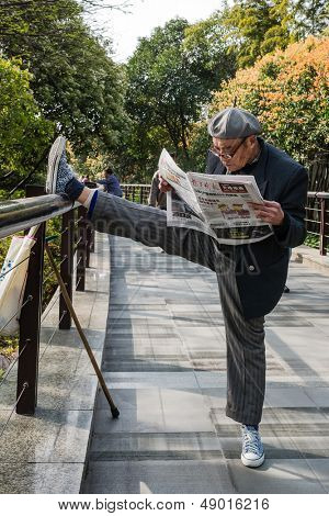 SHANGHAI - APRIL 7: one old man exercising stretching splits and reading newspaper in gucheng park  on april 7th, 2013 in Shanghai