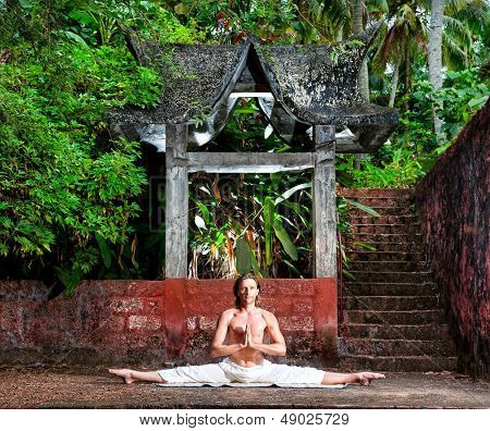 Yoga leg split by man in white trousers near stone temple in tropical forest poster