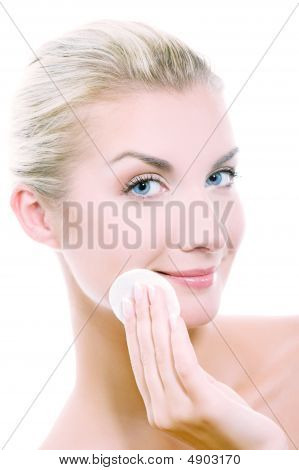 Beautiful Young Woman Removing Cosmetics With Cleansing Pad. Toned In Blue