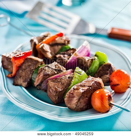 grilled beef shishkabobs on table close up poster