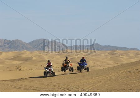 Three men riding quad bikes in a row at the desert