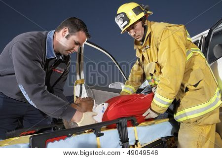 Side view of a fire fighter and paramedic assisting man at crash site