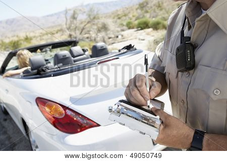 Closeup of a cropped police officer writing traffic ticket to woman sitting in car