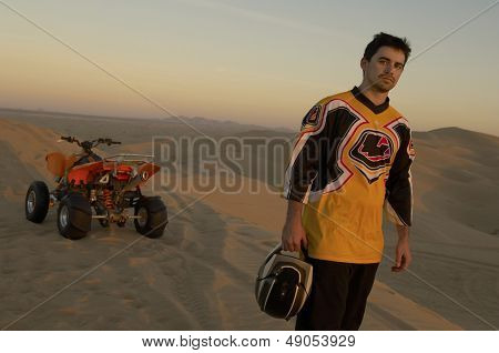 Man standing by quad bike in desert at sunset