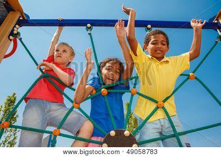 Three friends climbing the net