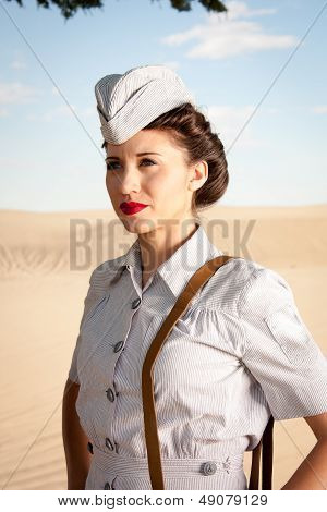 A beautiful young WWII nurse in authentic uniform stares off into the dry dusty landscape. close up head and shoulders. poster
