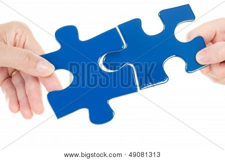 People Putting Two Pieces Of Jigsaw Together