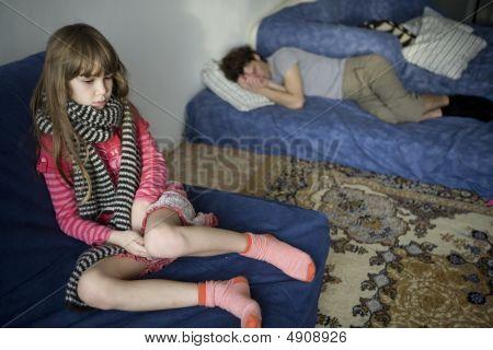 Little Cute Upset Girl In Scarf Sitting On Sofa.