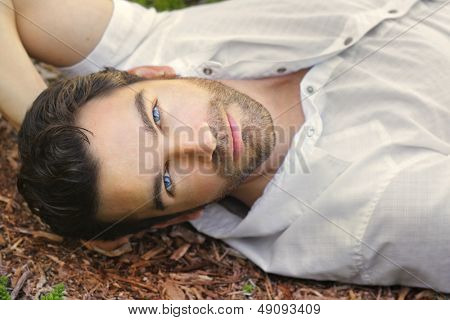 Portrait of young man outdoors with very handsome face in white casual shirt relaxing outdoors