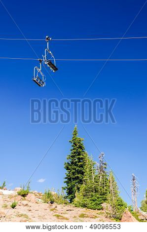 Ski lift with a deep blue sky passing over green pine trees in the summer on Mount Hood poster