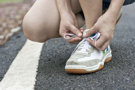 Runner tying running shoes getting ready for jogging