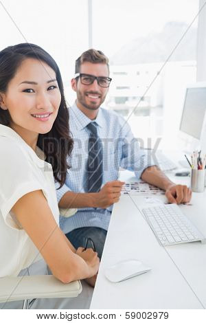 Side view of casual photo editors working on computer in a bright office