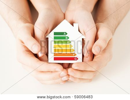 energy saving, real estate and family home concept - closeup of couple hands holding white paper house with energy efficiency rating
