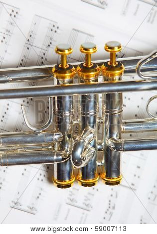 Close up part of silver B-flat trumpet on top of music sheet