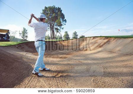 Golfer playing bunker shot
