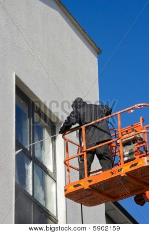 Worker In Cherry-picker Washing A Wall