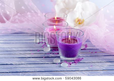 Beautiful colorful candles and  orchid flowers, on color wooden table, on light background