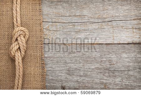 Ship rope on old wood and burlap texture background with copy space