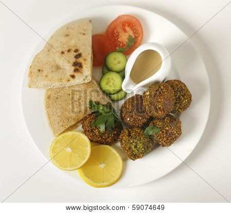 Homemade falafals (herbed and spicy chickpea balls) on a plate with Egyptian flat bread, lemon slices, tomato, cucumber and a tahina sauce, viewed from above