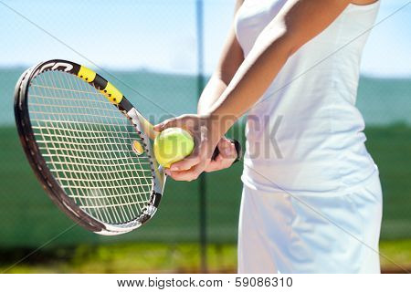 Player's hand with tennis ball and racket poster