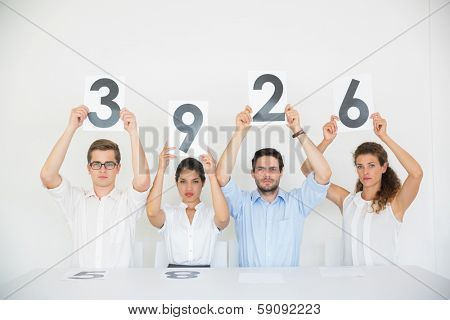 Portrait of business people holding score cards at desk in office