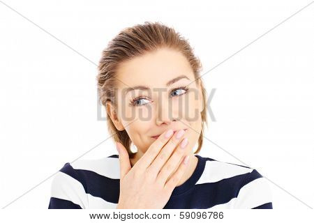 A portrait of a pretty woman covering her lips in a oops gesture over white background