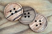 large Wooden sewing buttons on wooden background poster