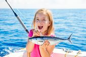 Blond kid girl fishing tuna little tunny happy with trolling catch on boat deck poster