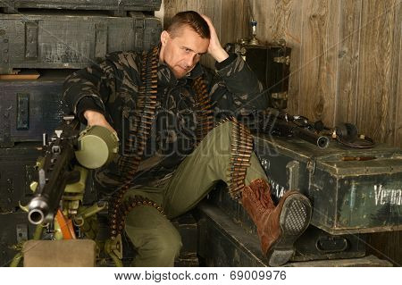Thoughtful armed soldier sits