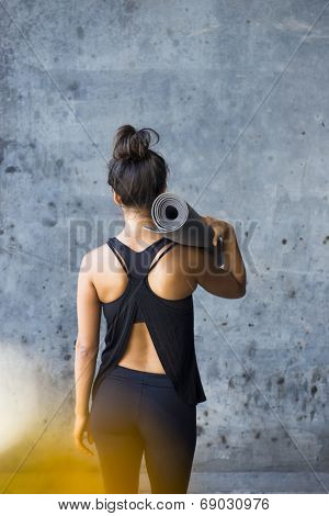 Woman ready to practice yoga in a urban enviromment