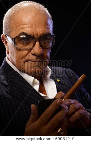 Old gangster holding mobilephone, smoking cigar, looking at camera serious.