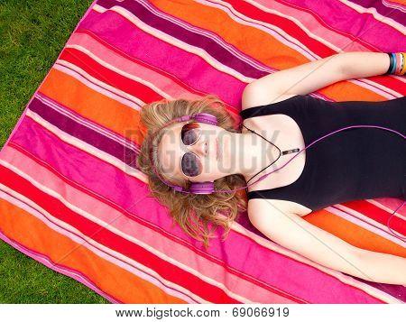 Beautiful Teenage Girl With Headphones Lying On Her Back On A Colorful Rug