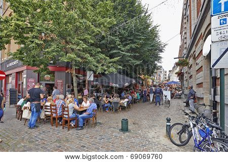 People Drink, Eat And Talk On The Terrace Of A Cafe