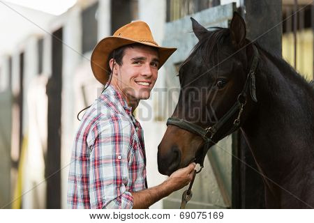 cheerful cowboy with a horse in stable