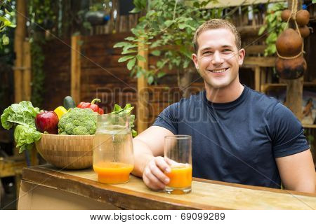 Young fitted man enjoying an organic juice and vegetable in a raw restaurant