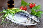 Salted herring on a wooden table with green onion tomatoes green basil and olive oil poster