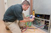 HVAC technician charging a heat pump with refrigerant poster