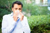 Closeup portrait of young man in blue shirt with allergy or cold blowing his nose with a tissue looking miserable unwell very sick isolated outside green trees background. Flu season vaccination. poster