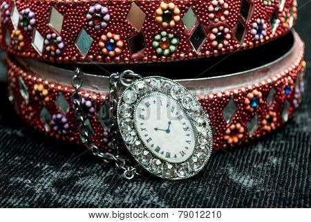 Old indian jewelery box with old watch on a chain.