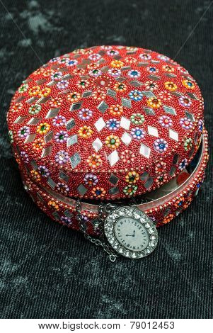 Old indian jewelery box with old watch on a chain. Vertical composition.