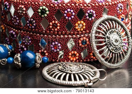 Old indian jewelery box with the closeup earrings on a wooden background.