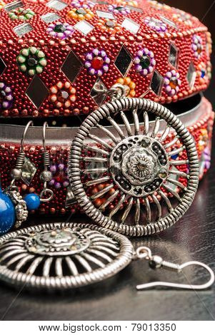 Old indian jewelery box with the closeup earrings on a wooden background. Vertical composition.