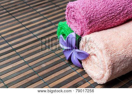 Spa towels rolls and flower lying on wooden mat. Space for your text. Horizontal composition.