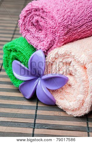 Closeup spa towels rolls and flower lying on wooden mat. Space for your text. Vertical composition.