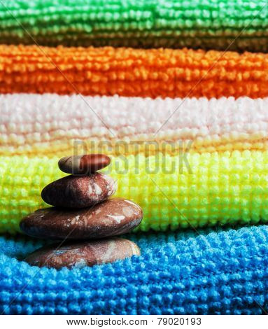 Closeup stack of colorful towels and tower of stones. ** Note: Shallow depth of field